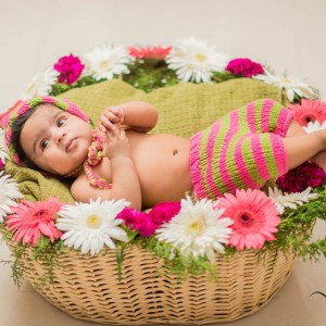 NM Clicks Baby in a basket of flowers