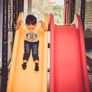 Kid enjoying on a slide at Tumble Town